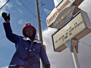Anthony Roberts is a seasonal worker for Liberty Income Tax Services on the corner of Madison and Edgewood avenues. He waves and paces around in the intermittent snow on March 25. (James Figy)