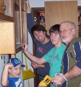 Hanging cabinets in my parents' kitchen with my dad and brothers.
